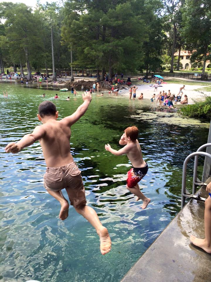 Two boys jumping off a diving platform.