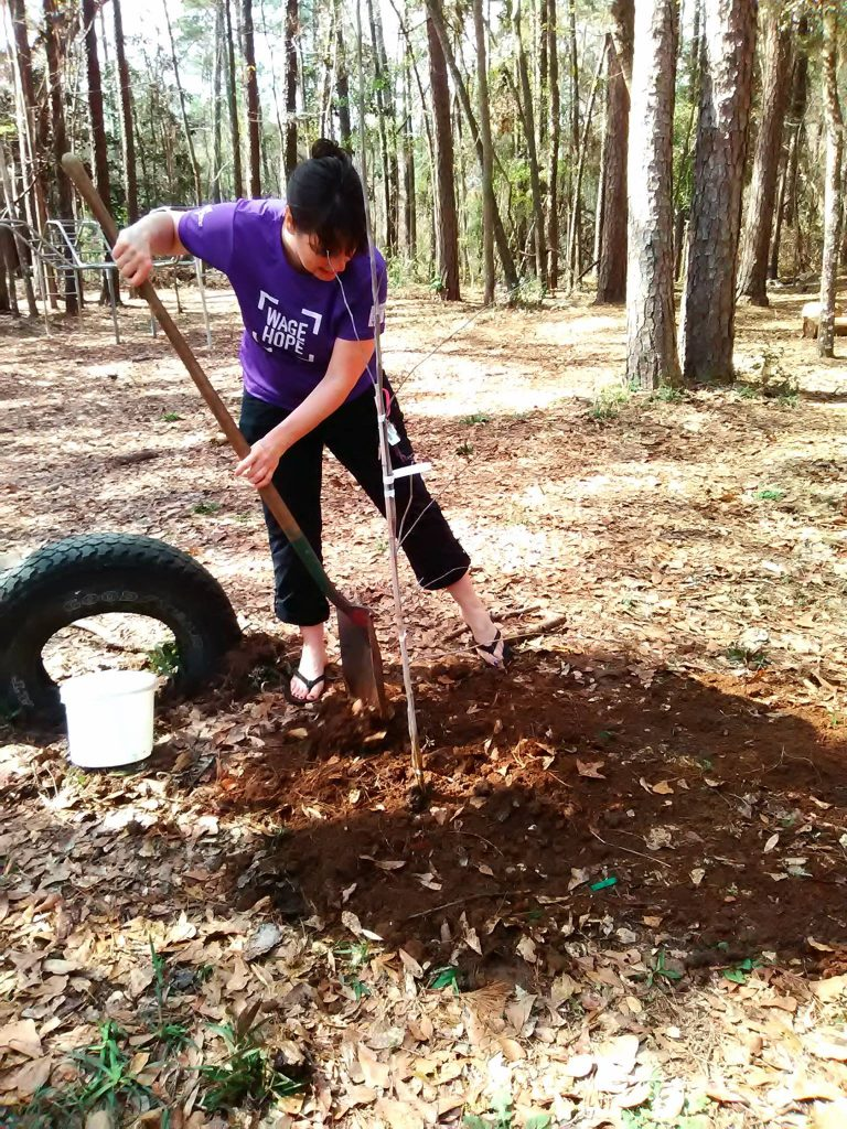Dark-haired woman digging with a shovel.