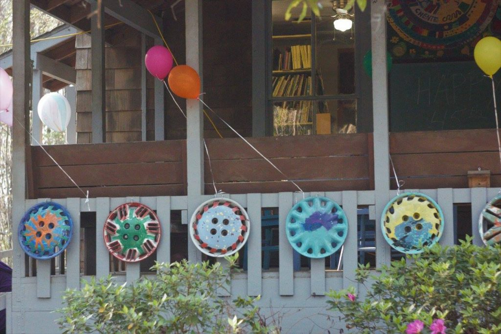 Bright balloons and colorful hubcap art lined the porch