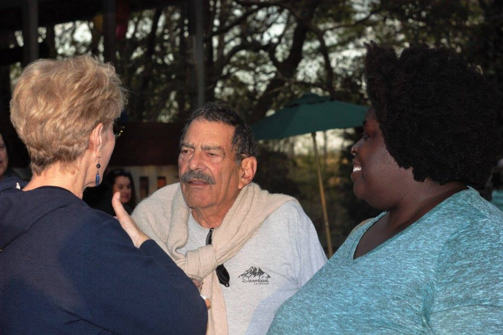 Two women talking to a man with a mustache. One woman has blonde hair and the other has dark hair.