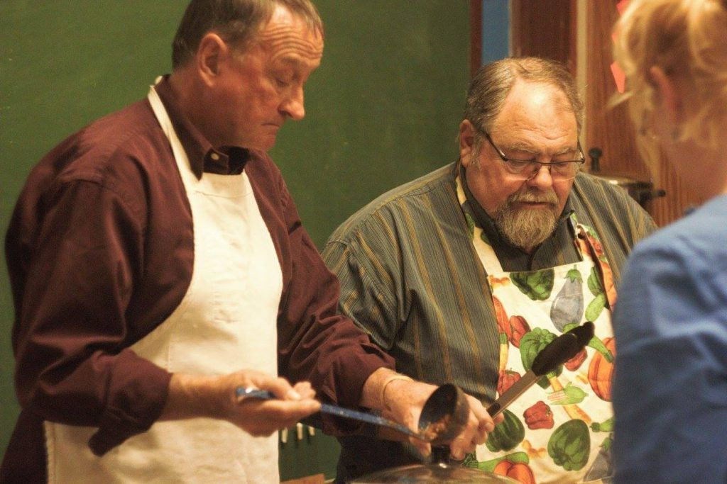 Two men in aprons serving food.