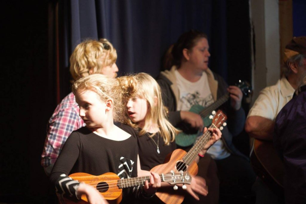 Five people of different ages and genders playing acoustic instruments.