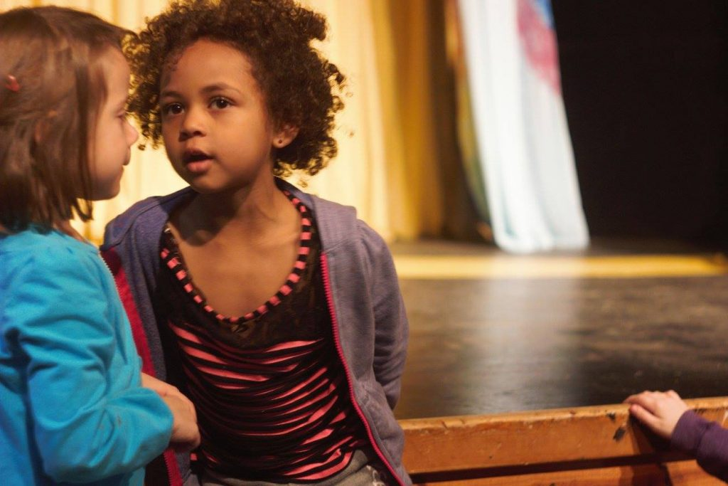 Two little girls standing in front of a stage, talking.
