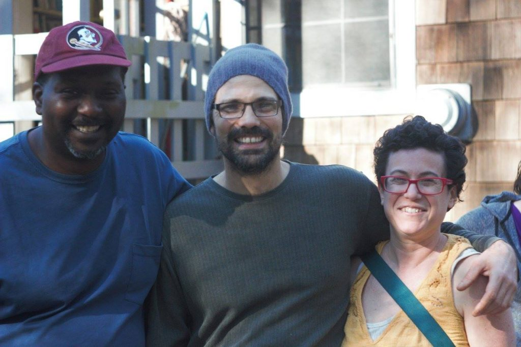 Two men and woman standing in a row, smiling. The man on the left is wearing a baseball cap, the man in the middle has on a knit cap and glasses, and the woman on the end has short hair and glasses.