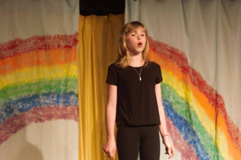 Young girl with blond hair singing. There is a rainbow behind her.